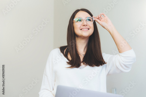 smiling glad female student searches information in websites makes