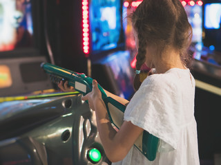 Little girl playing shooter game in theme park.