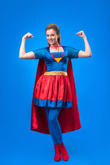 smiling woman in superhero costume showing muscles isolated on blue