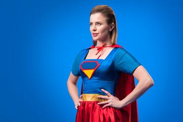 portrait of beautiful woman in superhero costume standing akimbo isolated on blue