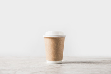 one disposable coffee cup on marble table on white