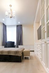 Спальня в светлых тонах с темной кроватью и синими шторами
