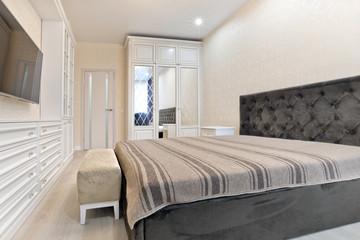 Спальня в светлых тонах с темной кроватью и телевизором мебелью