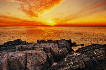 The coast of the Atlantic Ocean at dawn. A beautiful stony shore and a magnificent sky above the sea. USA, Maine.