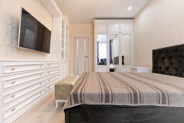 Спальня в светлых тонах с деревянной белой мебелью