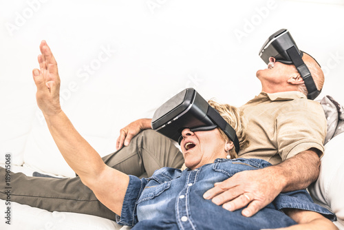 883ab5669d Senior mature couple having fun together with virtual reality headset  sitting on sofa - Happy retired