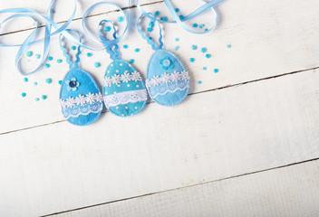 Handmade patchwork blue felt easter eggs on white wooden table