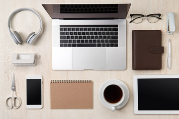 Overhead of office table with notebook, laptop, coffee cup and smartphone with copy space