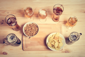 Beer mugs, glasses and beer snacks on wooden table. Top view.