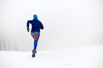 Girl trail running on snow in winter mountains