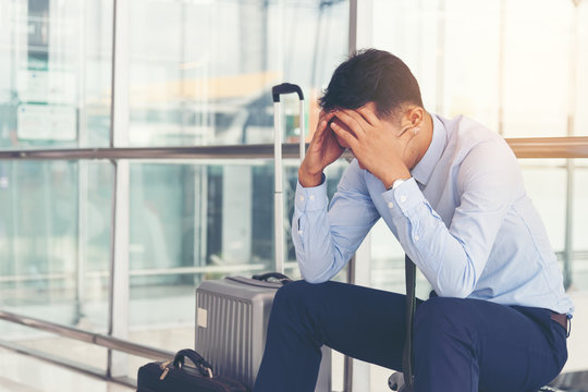 Serious businessman worrying something, sitting and touch his head at the airport terminal. Businessman miss his flight. Young man feeling sick before business trip.