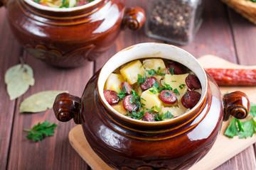 Dish cooked in a pot - potatoes, sausages, smoked in a clay pot on a wooden rustic background