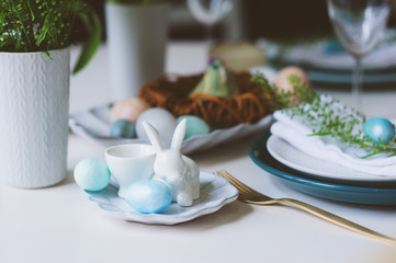 easter and spring festive table in nordic scandinavian style, decorated in blue and white natural tones with eggs, bunny, fresh flowers and candles.