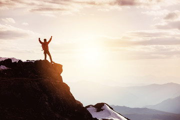 Man in winner pose at mountain top against mountains and sunset