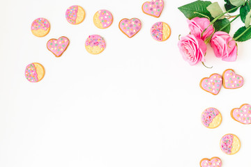 Gingerbread cookies with pink glaze and roses on white background. Flat lay. top view.