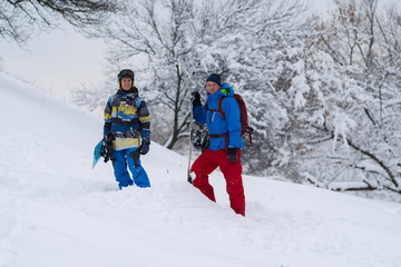 Two happy snowboarders are standing in the forest