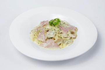 Spaghetti with ham and mushroom cream on white bowl and white Background