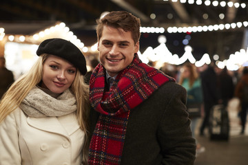 Portrait Of Couple Enjoying Christmas Market At Night
