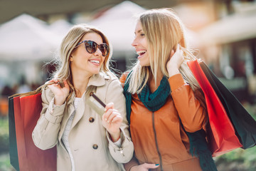 Happy friends shopping. Two beautiful young women enjoying shopping in the city holding credit card