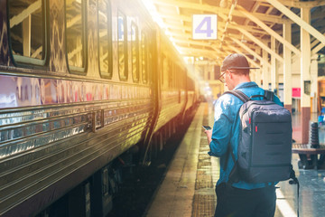 Man with backpack holding a phone in a train station with light