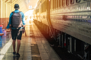 Man with backpack walking on the plateform in a train station