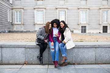 Three multiethnic women sitting together and watching smartphone at historic building in Madrid, Spain.