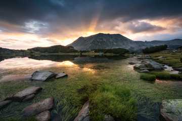 Pirin mountains / Magnificent sunrise view with first rays behind Todorka peak and Muratovo lake in Pirin mountains, Bulgaria