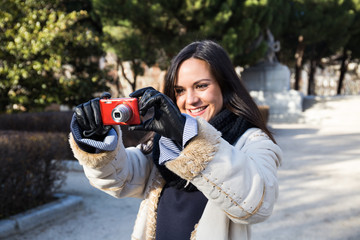 Pretty young smiling woman standing and taking shot with casual camera in park in Madrid, Spain.