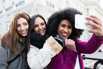 Happy young pretty women standing together and taking selfie on street in Madrid, Spain.