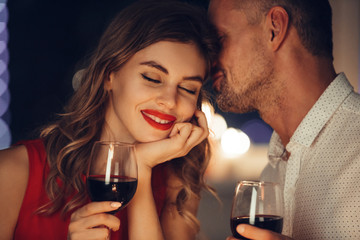 Young handsome man whisper to his woman while have romantic dinner Fototapete