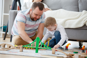 Picture of father playing with son in toys sitting on floor, sitting next to pregnant mother