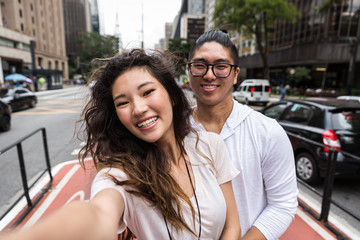 Asian Couple taking a selfie in Paulista Avenue, Sao Paulo, Brazil