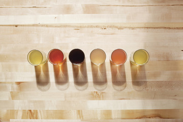 Aerial view of six glasses containing coloured liquid.