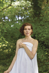 Young woman in woodland wearing towel.