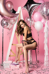Beautiful sexy slim girl wearing black erotic underwear posing with helium balloons, gifts, confetti on a pink background