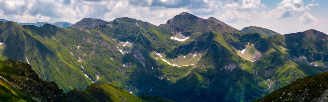 panorama of Fagaras mountain ridge. beautiful landscape with rocky cliffs and grassy slopes in summertime