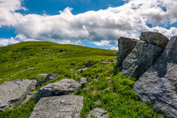 giant rocks on a hill in summertime. beautiful landscape under the blue sky with some clouds