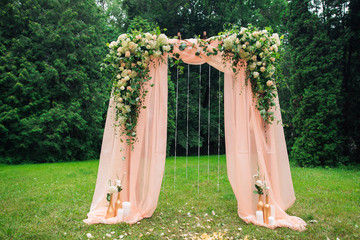 Beautiful place made with wooden square and floral roses decorations for outside wedding ceremony in green park. Wedding settings at scenic place. Horizontal color photography.
