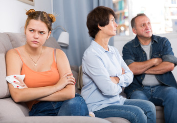 Adult couple is carefully talking with a sad daughter on sofa