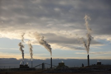 Emissions rising from the smoke stacks of a coal-fired power plant at sunset near Gillette, Wyoming / USA.