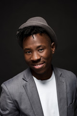 Portrait of attractive young black male studio with hat cheesy smile on dark background
