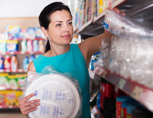 Woman choosing plastic plate and cup