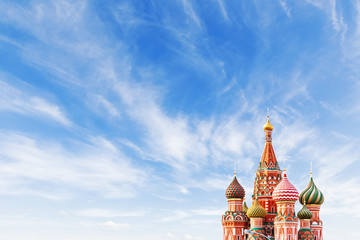 Domes of Saint Basil Cathedral on blue sky background. Famous landmark of Moscow, Russia. Bright sunny day with clouds. Cloudscape on blue sky. Place for text.