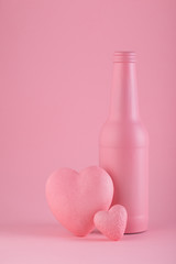 Pink mat bottle on the pink background with hearts. Love and St. Valentine's Day
