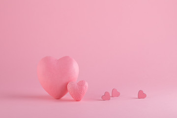Big and small hearts on the pink background. Love and St. Valentine's Day