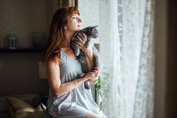 Lovely middle-aged redhead woman holding gray cat.