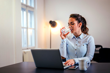 Smiling businesswoman drinking a glass of water at her desk in the office.