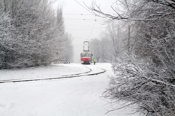 The red tram is riding along the snow-covered railway. Snow covered the railway running through the park and prevents the tram from traveling. Transport collapse due to snow.