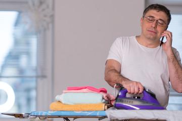 Modern and multitasking single man ironing and using his mobile phone