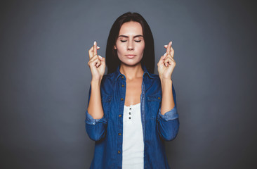 I would want that all happened. Attractive modern woman with closed eyes making a wish crossed fingers on a gray background isolated.